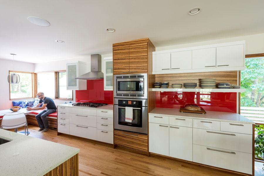 Kitchen with white cabinets and red backsplash