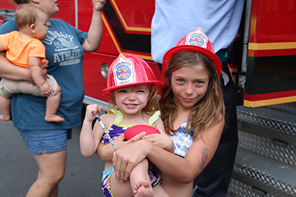 2 girls with fire hats in front of a fire truck