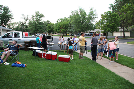 A crowd of people with coolers and lawn chairs at a block party