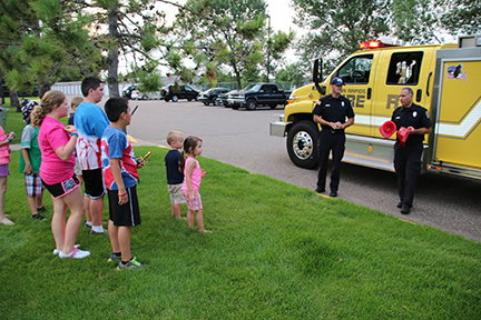 Firemen teaching a crowd of kids about fire safety